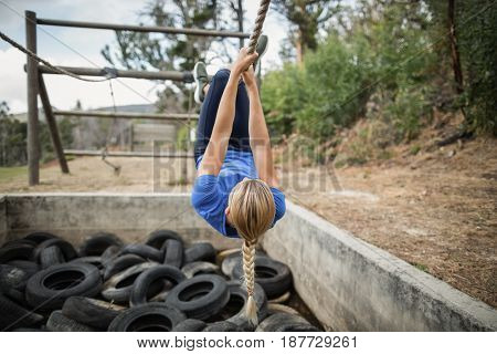 Woman climbing rope during obstacle course training at boot camp