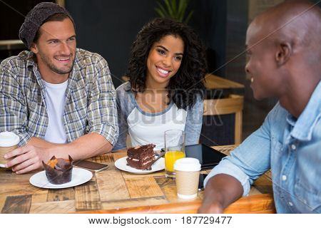 Happy multi ethnic friends talking at table in coffee shop