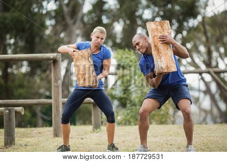 People carrying heavy wooden logs during obstacle course in boot camp