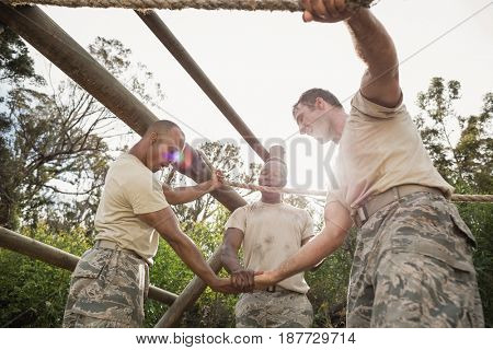 Military soldiers with hands stacked during obstacle training in boot camp