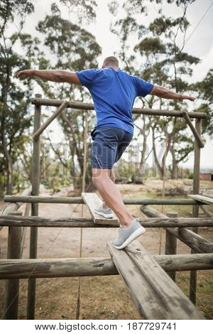 Fit man during obstacle course training at boot camp
