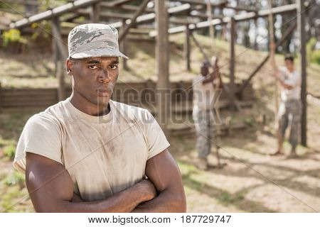 Portrait of military man standing with arms crossed during obstacle course in boot camp