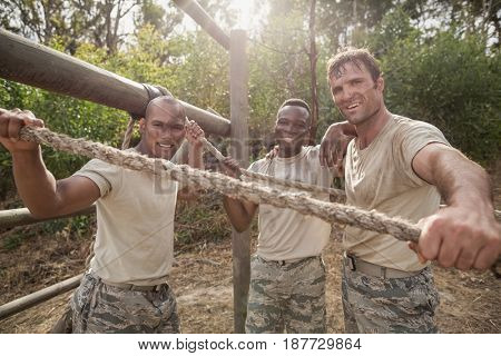 Portrait of military soldiers smiling during obstacle training at boot camp