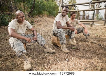 Military soldiers relaxing during obstacle training at boot camp