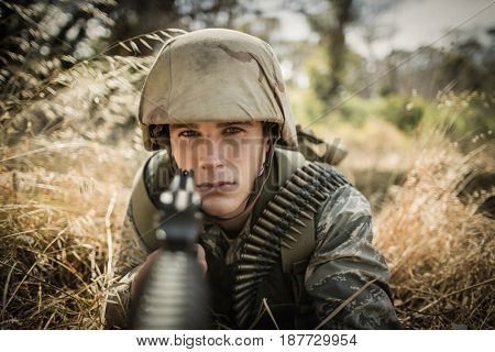 Portrait of military soldier aiming with a rifle in boot camp
