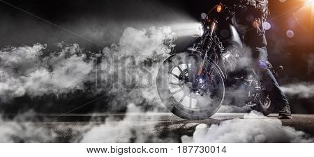 Close-up of high power motorcycle chopper with man rider at night. Fog with backlights on background.