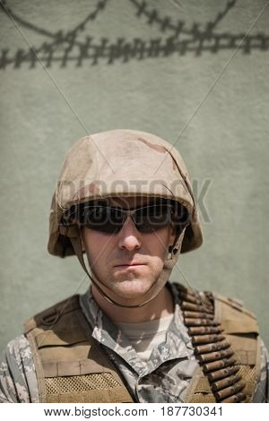 Close-up of confident military soldier standing against concrete wall in boot camp