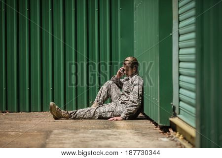 Military soldier talking on mobile phone in boot camp