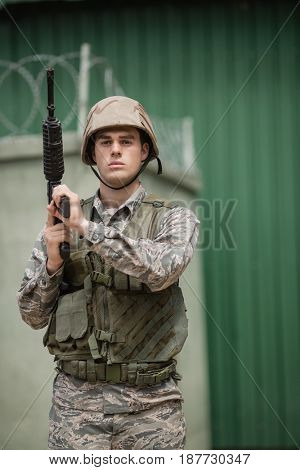 Military soldier standing with a rile in boot camp
