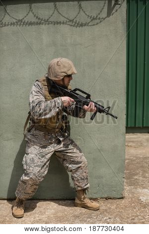 Military soldier aiming with a rifle against concrete wall in boot camp