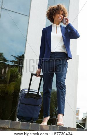 Businesswoman with luggage bag talking on mobile phone near office building
