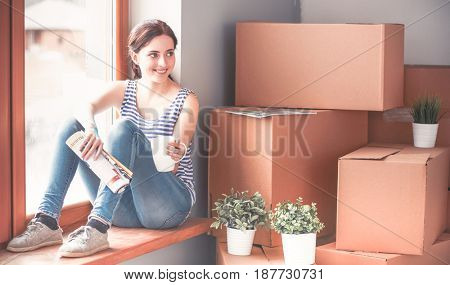 Girl sitting on windowsill at new home with cup