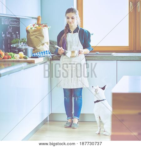 Portrait of young woman standing against kitchen background