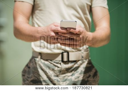 Mid section of military soldier using mobile phone in boot camp