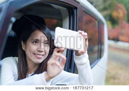 Woman using cellphone to take photo inside a car