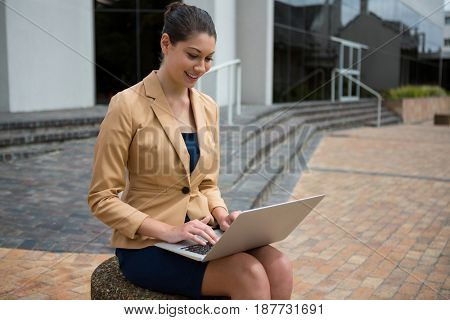 Smiling businesswoman using laptop in the office premises