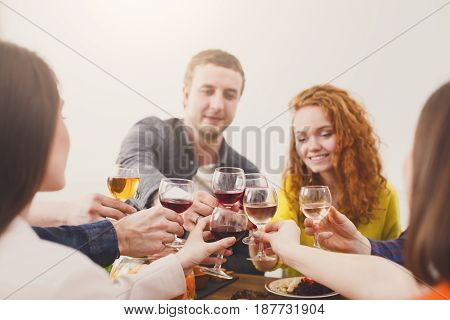 Happy couple celebrate with friends, drink wine, have dinner in restaurant or at home party. People have meals together, friendly conversation