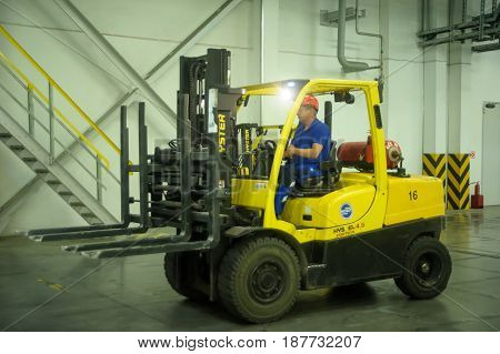 Tobolsk, Russia - July 15. 2016: Sibur company. Polymer plant. Driver on forklift truck loads pallets with finished goods from packaging machine