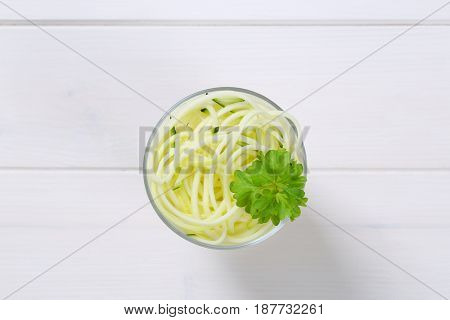 glass of raw zucchini noodles on white wooden background