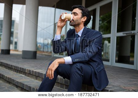 Businessman drinking coffee from disposable cup near office entrance