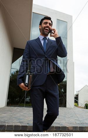 Businessman talking on mobile phone near office building
