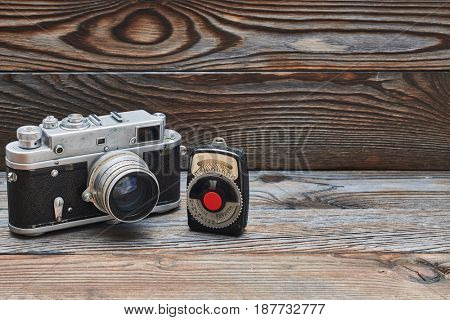 Vintage old retro 35mm rangefinder camera and light meter on wooden background with copy space