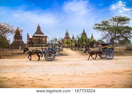 BAGAN, MYANMAR-MARCH 8, 2017: Tourists use horse drawn carriage for travel around ancient Bagan on March 8, 2017, Myanmar.(Burma)