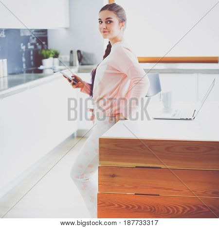 Woman using mobile phone standing in modern kitchen