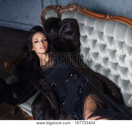 Beautiful and young woman posing in black dress on grey sofa. Vintage interior and retro background.