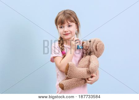 Cute little girl holding inhaler and toy bear on color background. Allergy concept