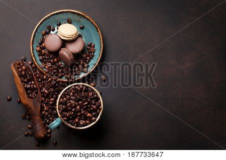 Coffee cup with roasted beans and macaroons on stone background. Top view with copy space for your text