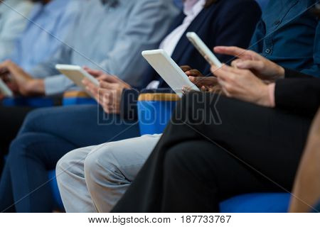 Business executives participating in a business meeting using digital tablet at conference center