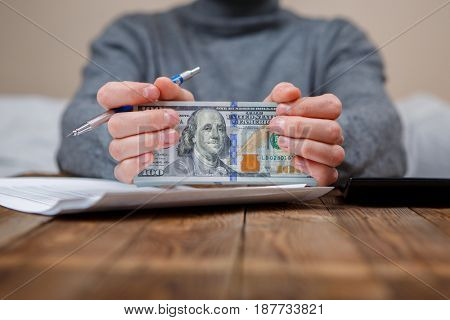 Caucasian hands counting dollar banknotes on dark wooden table