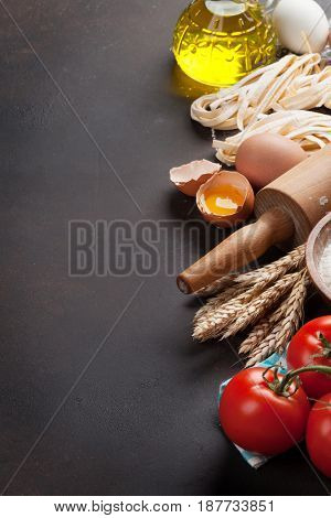 Pasta cooking ingredients on wooden kitchen table. With space for your text