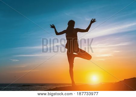Yoga silhouette. Meditation girl on the sea during sunset. Fitness and healthy lifestyle.