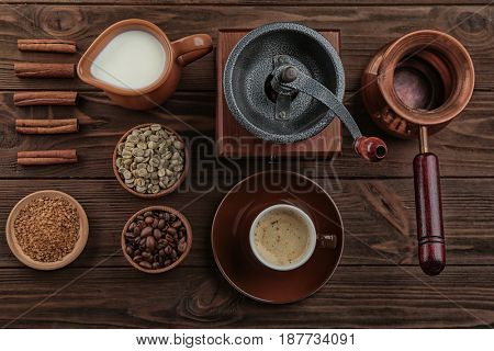 Fresh coffee with ingredients and accessories on wooden background