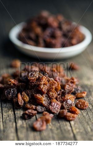 Sweet dried raisins on old wooden table.