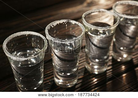 Row of tequila shots on wooden background