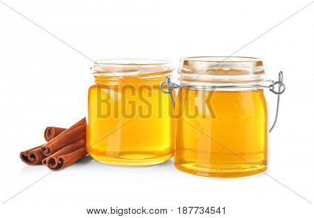 Cinnamon sticks and honey in jars isolated on white
