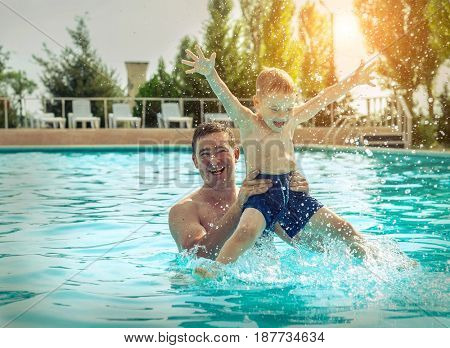 Father and son funning in water pool under sun light on summer day. Leisure and swimming at holidays.