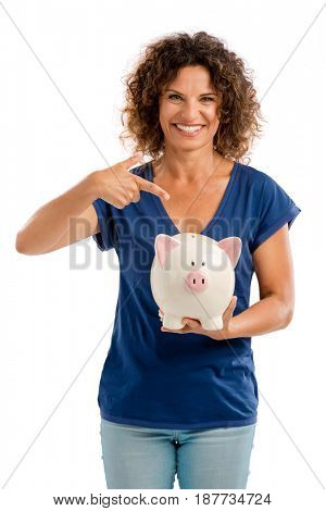 Portrait of a happy middle aged woman pointing to a Piggybank