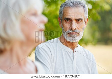 Old man staring pensive at a woman in summer in the nature