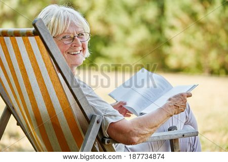 Old happy lady reading a book and smiling in summer in the nature