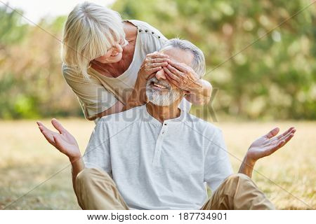 Old woman covers her husband's eyes from the back in summer in the nature