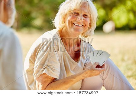 Old woman winning the card game and having fun in the garden