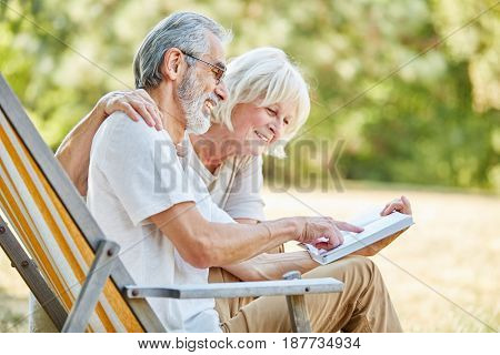 Senior couple reading a book together and laugh happily