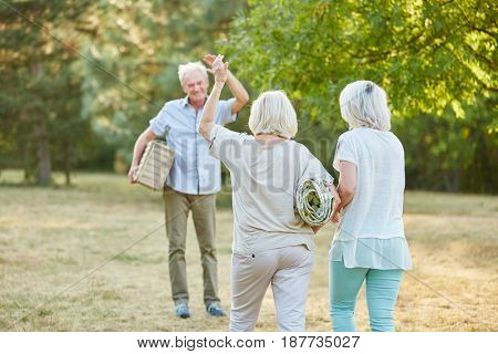 Group of seniors meets up at the park for a picninc in the nature