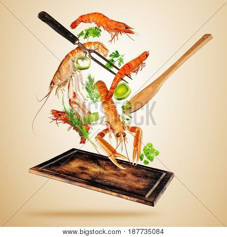 Fresh sea food, prawns and lobsters flying above wooden board, isolated on brown background. Food preparation, fresh meal ready for cooking. Extra high resolution