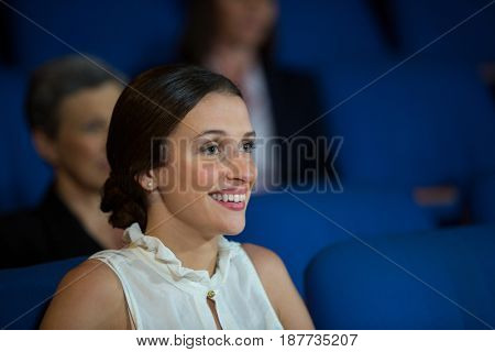 Female business executive listening to speech at conference center