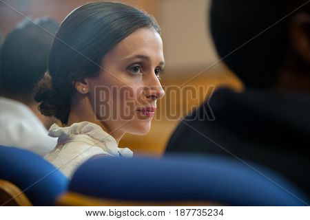 Female business executives listening to speech at conference center